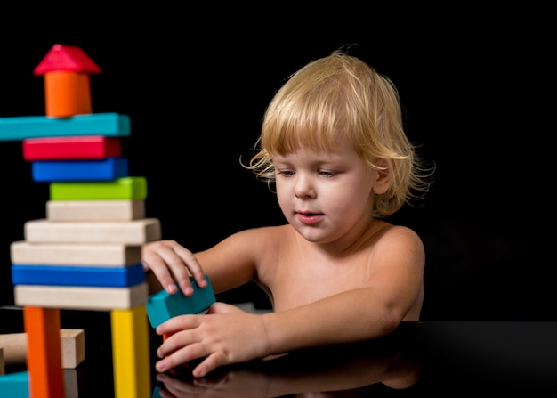 Ребенок с расстройством аутистического спектра строит дом из деревянного конструктора