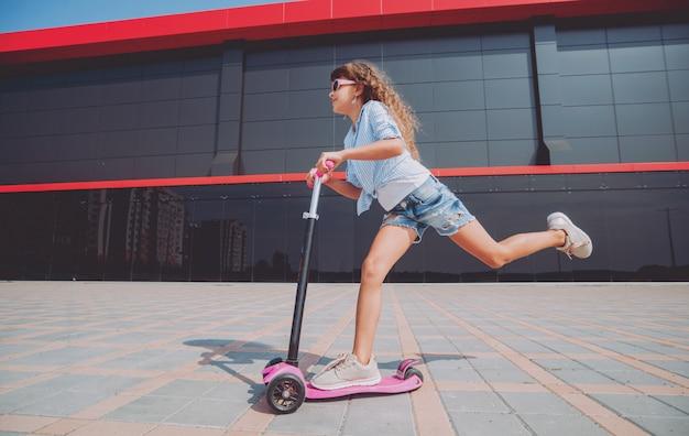 屋外のスクーターに乗る少女。街路景観