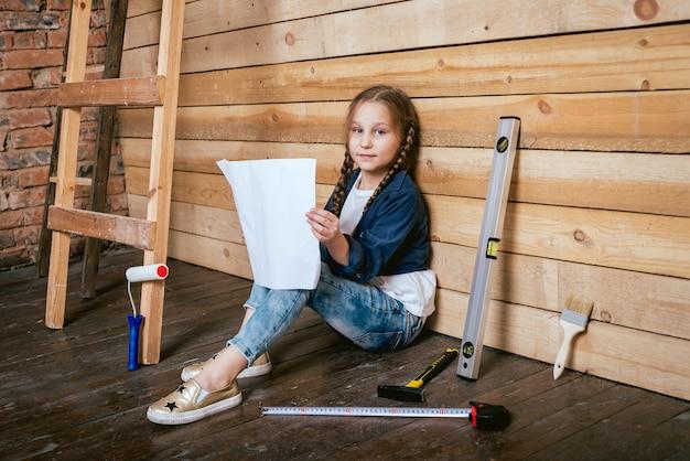 Маленькая девочка в комнате с деревянной стеной. строительство
