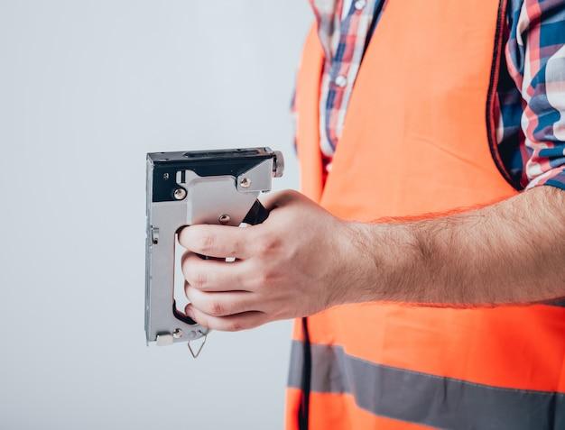 家の改修のためのツールを保持している手。灰色の風景
