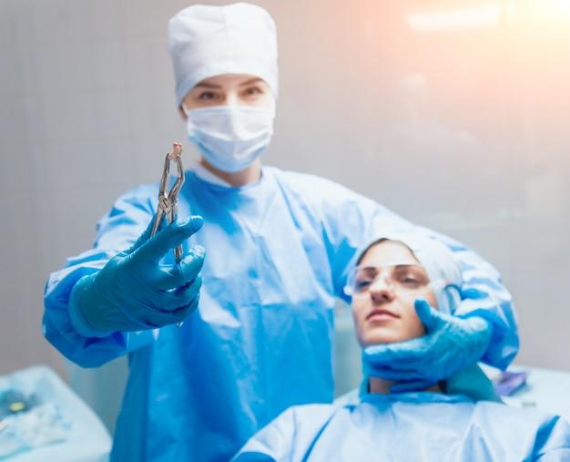 Стоматолог с помощью хирургических плоскогубцев, чтобы удалить гниющий зуб. современная стоматологическая клиника