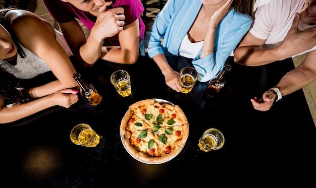 Веселые друзья в пабе. пили пиво, ели пиццу, разговаривали, веселились.