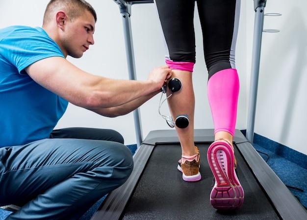Физиотерапевт устанавливает электростимулятор на мышцы ног.