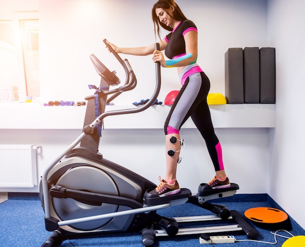 Молодая спортивная женщина с электростимулятором на мышцах ног.