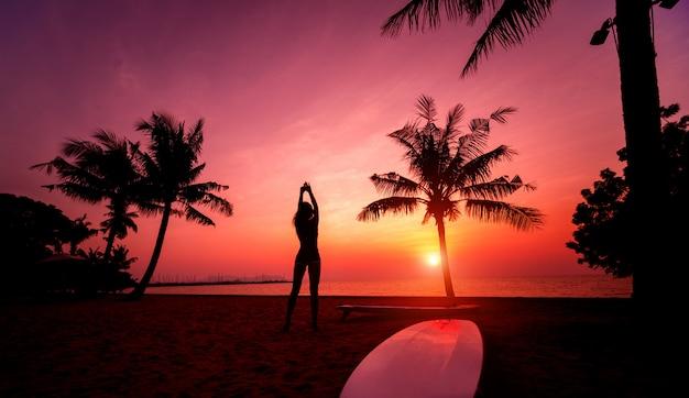 熱帯のビーチで夕暮れ時の長いサーフボードとサーファーの女の子のシルエット
