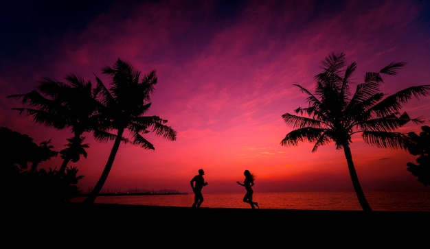 Силуэт пары на тропическом пляже во время заката на фоне
