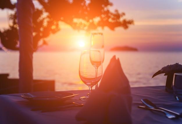 バーのテーブルにワイングラス。海に沈む夕日