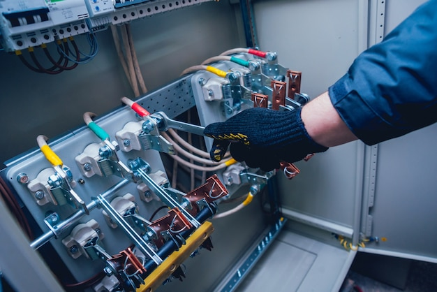 電気技師は手で電気ボックスのスイッチをテストします。ヒューズ付き電気パネル