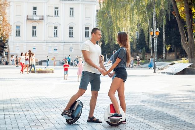 Молодая пара вождения на моноколесе в парке