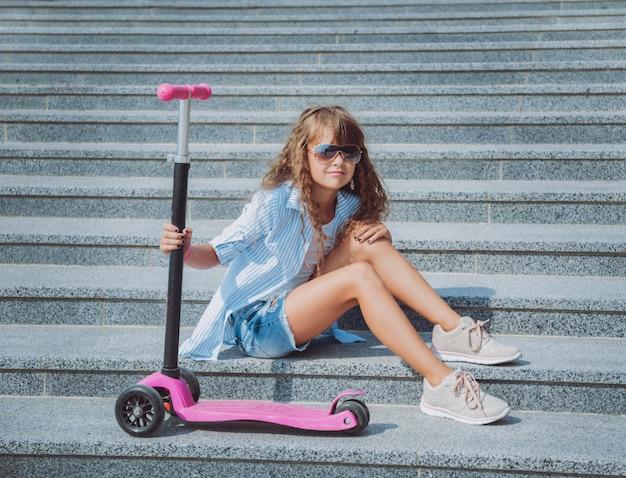 スクーターを屋外でポーズの女の子。ストリートシティ