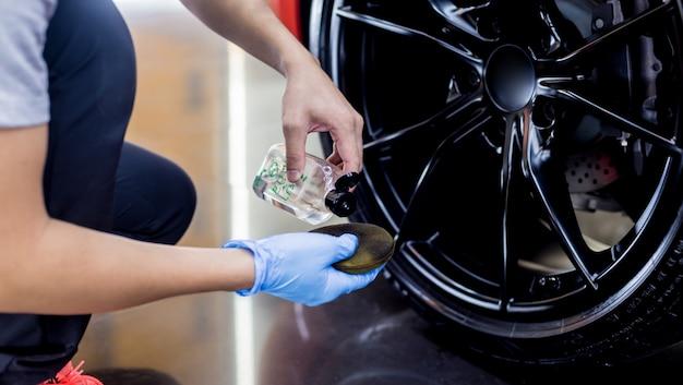 Работник автосервиса полирует колеса автомобиля тканью из микрофибры.