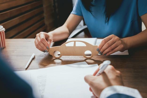 自動車保険に署名する男、エージェントは木造車のモデルを持っています。