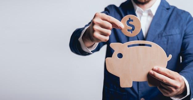 Бизнесмен держит монету под деревянным поросенком.
