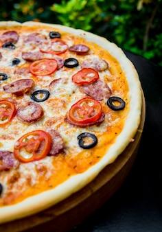 木製のテーブルに大きなピザ。