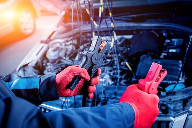 アキュムレータ充電。手と端末。自動車修理。