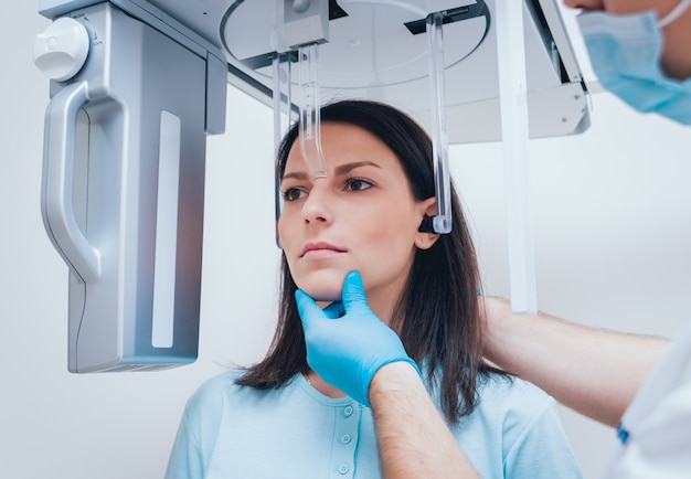 Пациент молодой женщины стоя в рентгеновском аппарате.