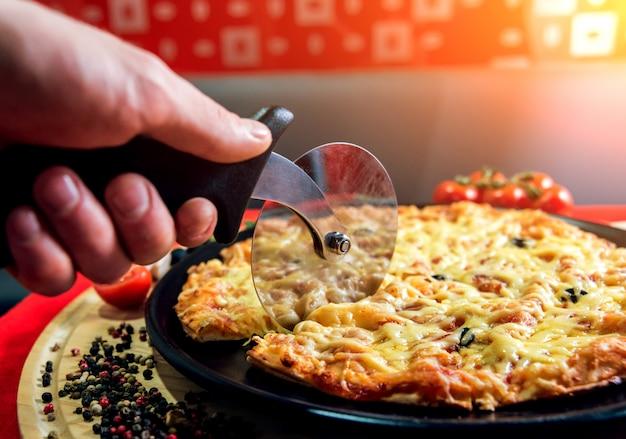 Повар готовит пиццу. он кладет сыр. нарезать пиццу на кусочки.