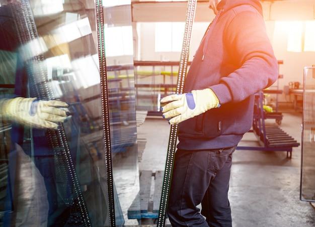 Рабочие переносят стекло. на фабрике по производству окон и дверей