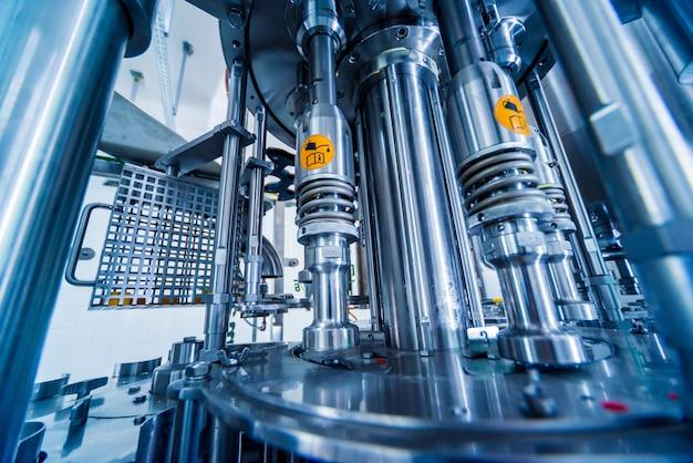 Автоматическая разливочная машина наливает воду в пластиковые пэт-бутылки.