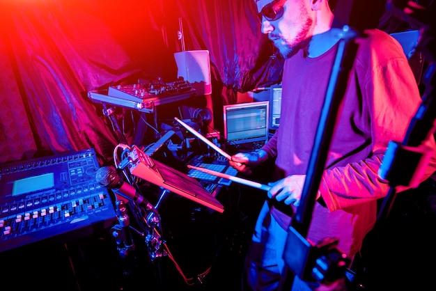 Молодой человек играя на электрическом барабанчике в студии звукозаписи.