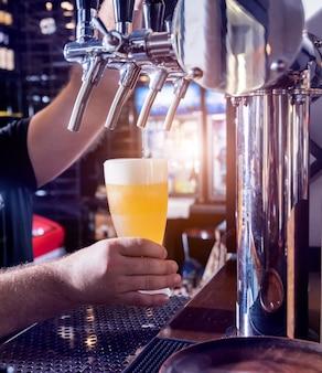 Бармен разливает разливное пиво по бокалам в баре.
