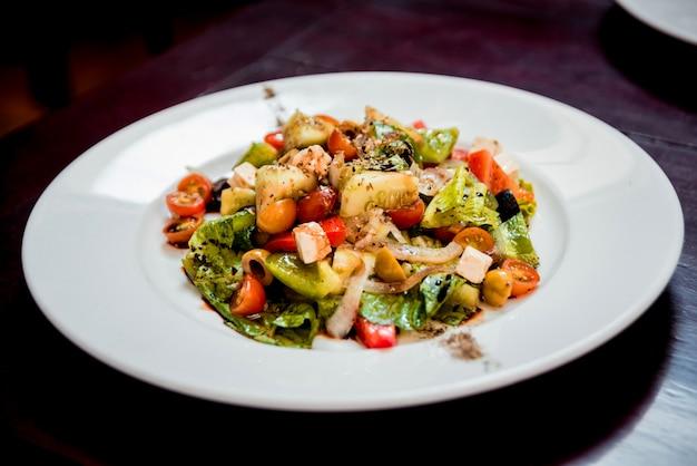 白い皿に新鮮なサラダ。飲食店。