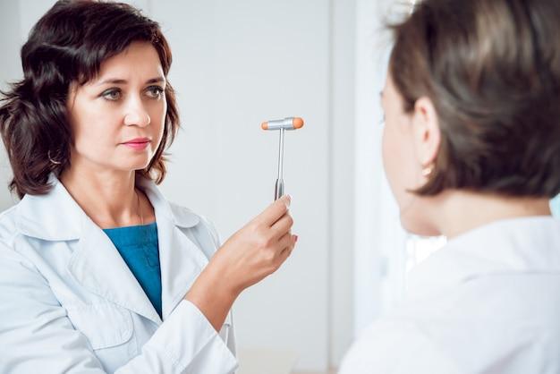 Неврологическое обследование. невролог проверяет рефлексы на пациентке с помощью молотка.