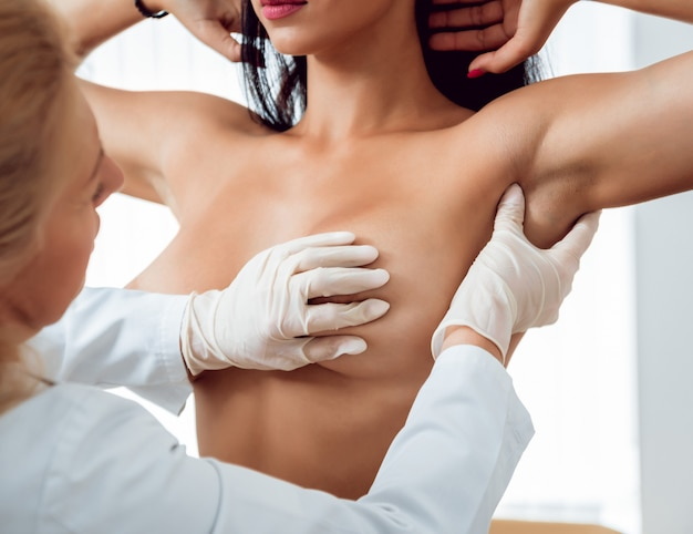 医者は若い女性の乳房を調べる。婦人科医との相談。
