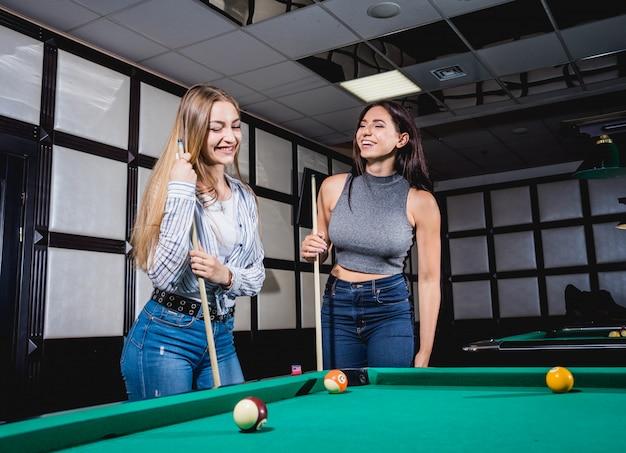 Две молодые женщины играют в бильярд.