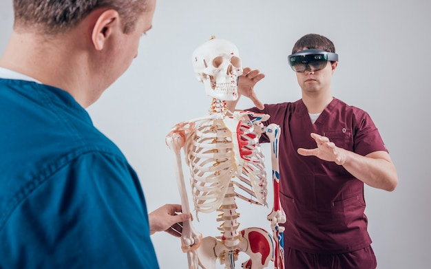 医者は学生を教えるために拡張現実ゴーグルと人間の骨格を使用します