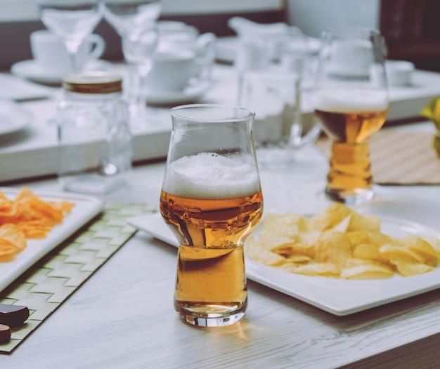 大きな白いテーブルの上のビールとチップ