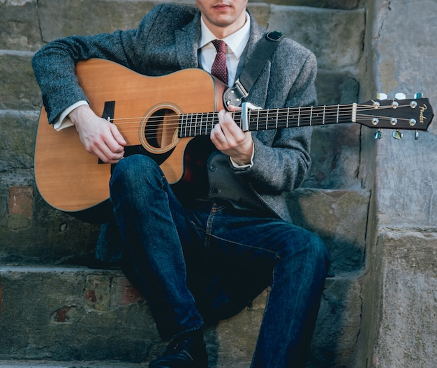 アコースティックギターを弾く男の手。本物の背景。