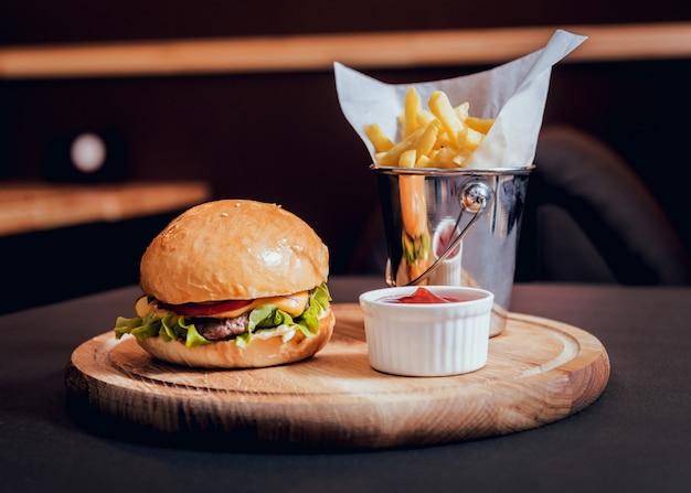 木製の机の上の火で大きくておいしいハンバーガー。