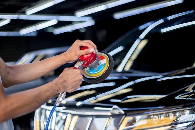 労働者は電動工具で車を磨きます。