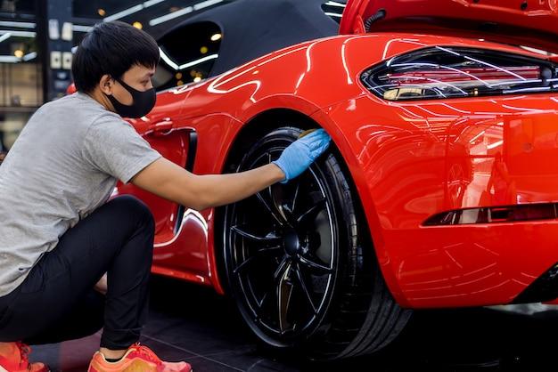 車のサービスワーカーがマイクロファイバーの布で車のホイールを研磨します。
