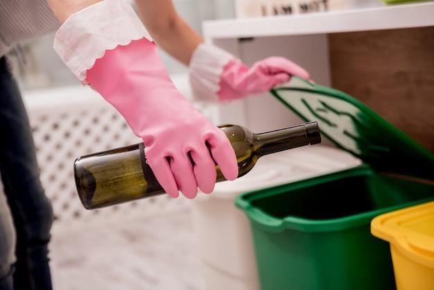 若い女性が台所でゴミを分別
