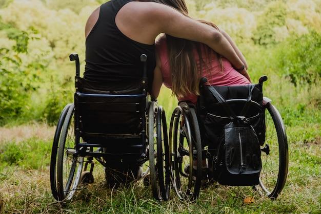С ограниченными возможностями пара отдыхает в лесу возле озера. инвалидные коляски в лесу на естественном фоне