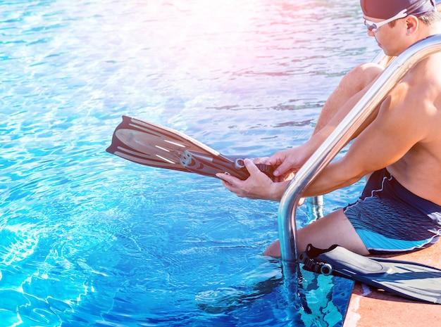 Молодой спортивный человек в ластах у бассейна