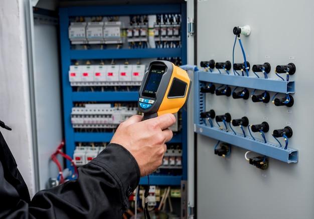 Техник использует инфракрасную тепловизионную камеру для проверки температуры в блоке предохранителей