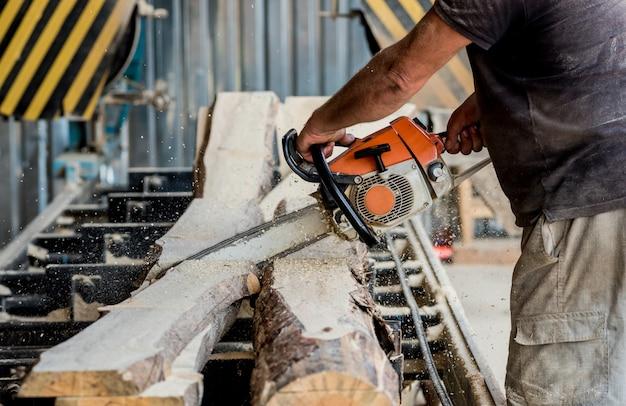 製材所でチェーンソーで木こり切断木。現代の製材所。丸太からボードを製材する業界。