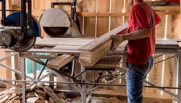 Современная лесопилка. плотник работает на деревообрабатывающем станке.