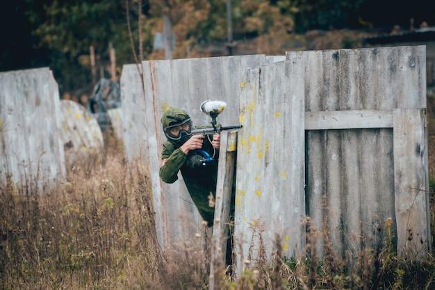 ペイントボールで遊ぶ銃を持つ男。屋外