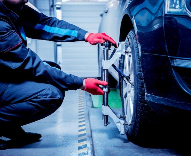 自動車整備士がサスペンション調整中にセンサーを取り付けます。