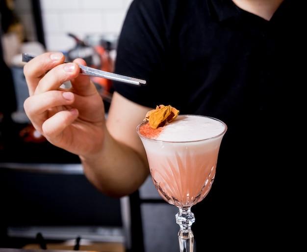 バーテンダーがバーカウンターでカクテルを作っています。新鮮なカクテル。仕事でバーテンダー。レストラン。ナイトライフ。