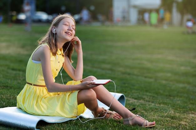 緑の芝生の上に座って、音楽、スマートフォン、ヘッドフォン、ライフスタイルを聞いて黄色のドレスで幸せな女の子