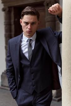 Портрет молодого красивого модного человека против деревянной стены в черном костюме & бабочке.