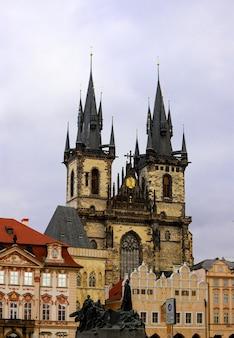 曇りの日にヤンフスの記念碑とプラハの教会。