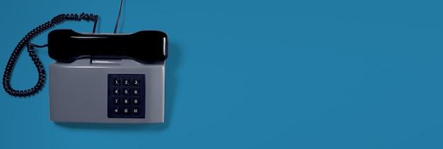 Серый старинный телефон с синей поверхностью