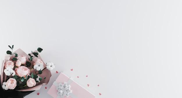 白い背景に白いリボンとピンクのプレゼントボックスと牡丹の美しいモダンな花束。