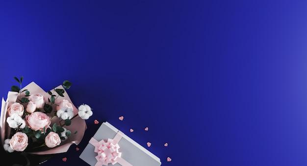 Красивый современный букет пионов с белой настоящей коробкой с розовой лентой на синем фоне.